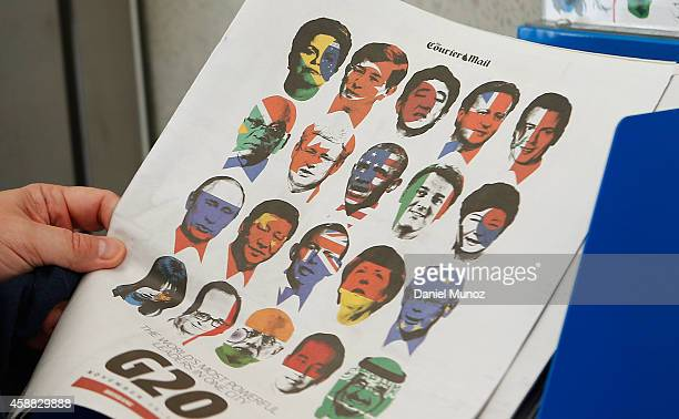 A woman takes a copy of a local newspaper with the G20 leaders faces painted in their own country flag colors at Brisbane airport on November 12 2014...