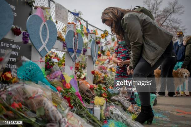 Woman takes a moment to herself at a makeshift memorial set up outside the site of a shooting at a King Soopers grocery store on March 25, 2021 in...