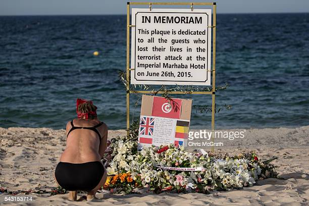 A woman takes a moment to remember the victims of the 2015 Sousse Beach terrorist attack at a memorial sign on the beach in front of the Imperial...