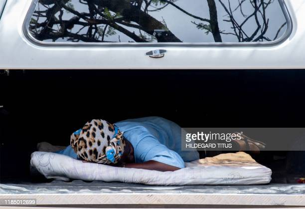 A woman takes a nap in the back of a vehicle outside the Mandume Primary School olling station in Katutura Windhoek on November 27 2019