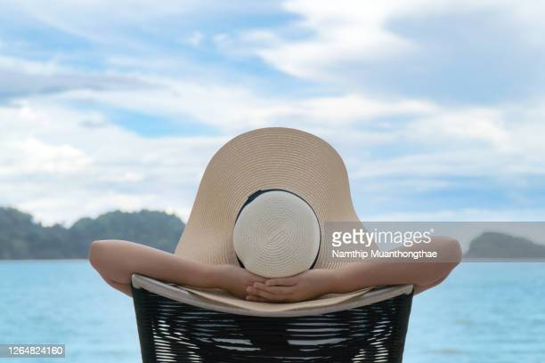 woman takes a nap on the beach chair with her hat at the beach for relaxing time in the summer holiday. - hat stock pictures, royalty-free photos & images