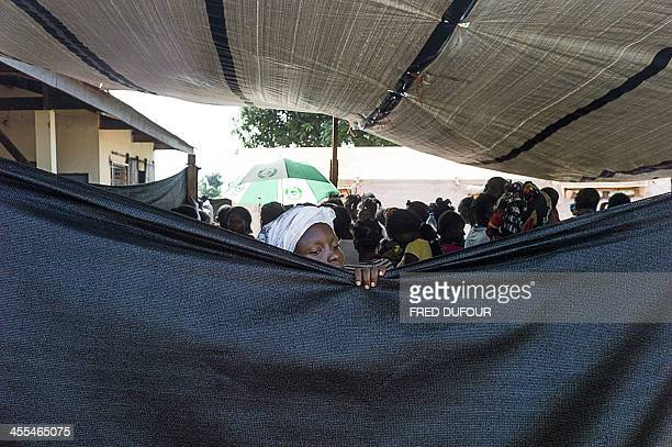 A woman takes a peek at doctors working at a mobile clinic set up by Doctors Without Borders at a camp for internally displaced persons near the...