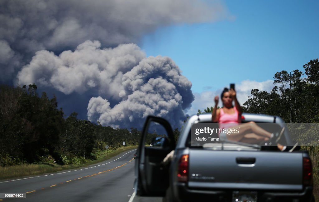 A woman takes a photo as an ash plume rises from the Kilauea volcano on Hawaii's Big Island on May 15, 2018 in Volcano, Hawaii. The U.S. Geological Survey said a recent lowering of the lava lake at the volcano's Halemaumau crater 'has raised the potential for explosive eruptions' at the volcano.
