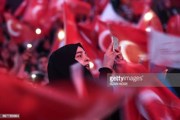 A woman takes a photo as supporters wawe Turkey's national flags during a campaign rally of Turkey's president on April 12 2017 during a 15 July...