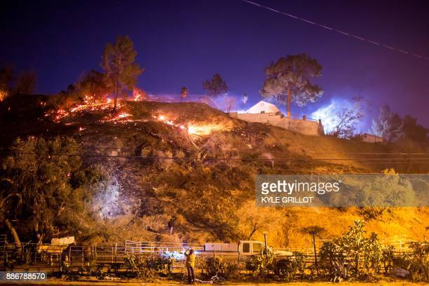 TOPSHOT A woman takes a photo as the Creek Fire burns behind a hillside near houses in the Shadow Hills neighborhood of Los Angeles California on...