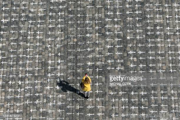 Woman takes a photo at the Old Town Square in Prague, on March 22 where thousands of crosses have been drawn onto the pavement to commemorate the...