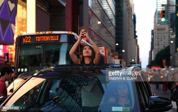 A woman takes a photo from the sunroof of a car as the sun sets as seen from 42nd street in Times Square in New York City on July 12 2018 during...