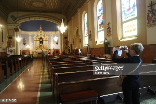A woman takes a photo in St Mary's Church originally constructed in 1845 as an addition to the Old Ursuline Convent on April 17 2018 in New Orleans...