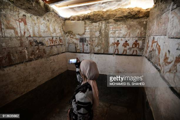 TOPSHOT A woman takes a photo inside the tomb of an Old Kingdom priestess adorned with wellpreserved and rare wall paintings on the Giza plateau in...