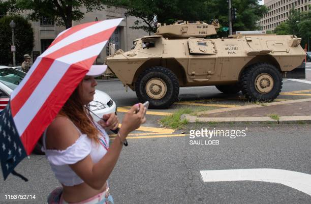 Woman takes a photo near an armored military vehicle during the Fourth of July parade in Washington, DC, July 4, 2019.A Humvee is parked on a street...