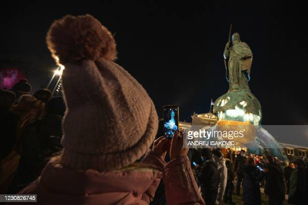 Woman takes a photo of a 23-metre tall statue, erected in honour of the 12th-century Serbian prince Stefan Nemanja, after the unveiling ceremony in...