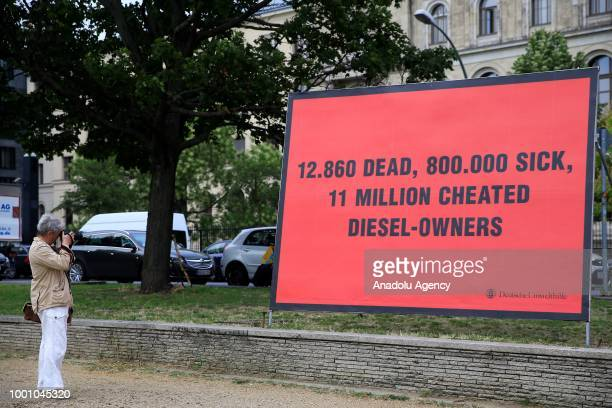 A woman takes a photo of a banner reading '12860 dead 800000 sick 11 million cheated dieselowners' that was placed by a part of German Environmental...