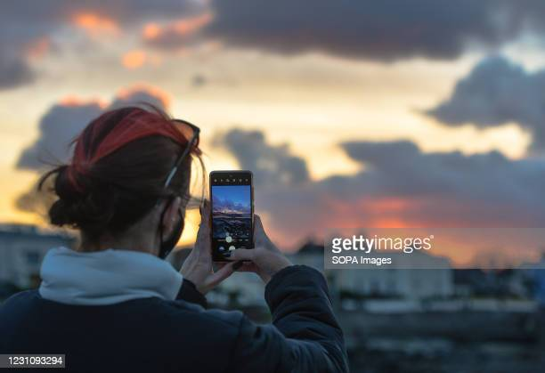 Woman takes a photo of a dark sky and sunset over Dún Laoghaire area in Dublin.