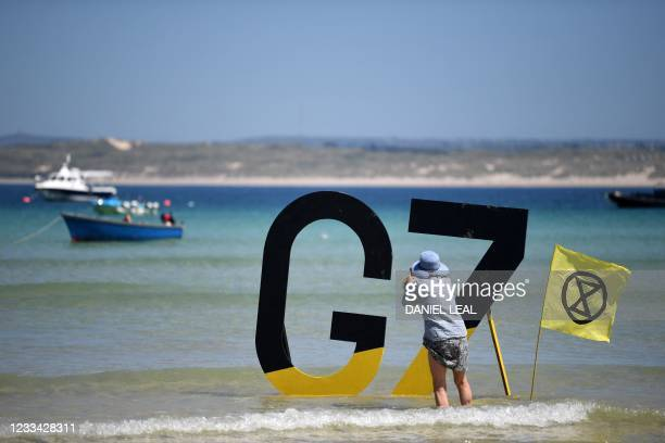 Woman takes a photo of a G& sign beside an Extinction Rebellion flag in St Ives, Cornwall during the G7 summit on June 13, 2021.