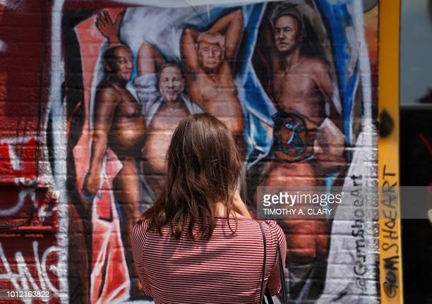 A woman takes a photo of a graffiti mural in the Williamsburg section of Brooklyn New York on August 6 2018 by New Yorkbased artist Angela China with...