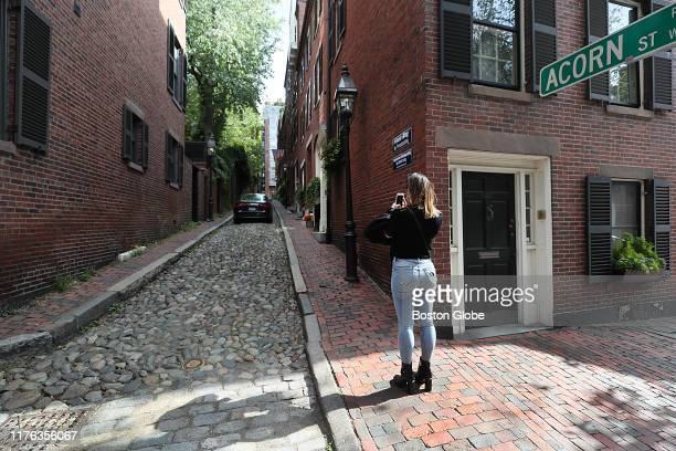 A woman takes a photo of Acorn Street in Boston on Oct 7 2019 Acorn Street on Beacon Hill has been dubbed by at least two websites as the most...