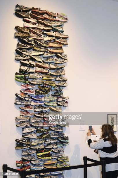 A woman takes a photo of an artwork featuring sneakers that had been left at the scene of the 2013 Boston Marathon bombings on display at a museum in...