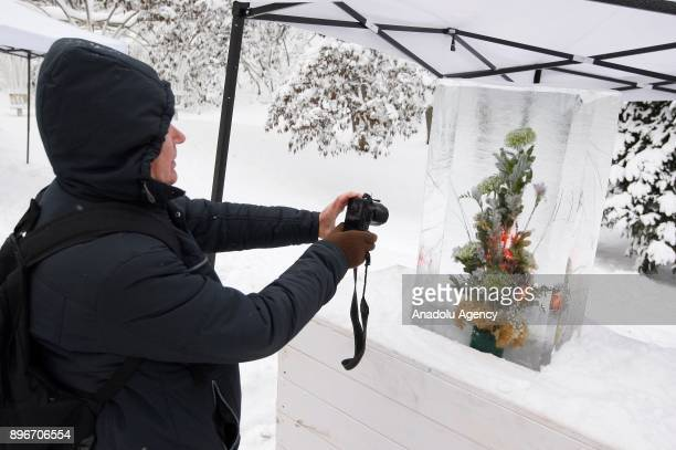 A woman takes a photo of an icecovered flower bouquet during the New Year's festival 'Ice Age' on the Pevcheskoye Field in Kiev Ukraine on December...