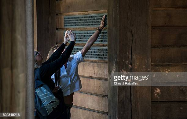 A woman takes a photo of another woman touching a name of their friend on the list of British victims of the 9/11 terroism attacks at the September...