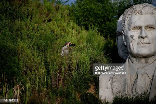 A woman takes a photo of decaying busts of former US Presidents during a photography workshop organized by John Plashal August 25 in Williamsburg...
