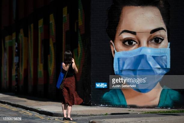 Woman takes a photo of graffiti on Brick Lane in East London on April 23, 2020 in London, England. The British government has extended the lockdown...