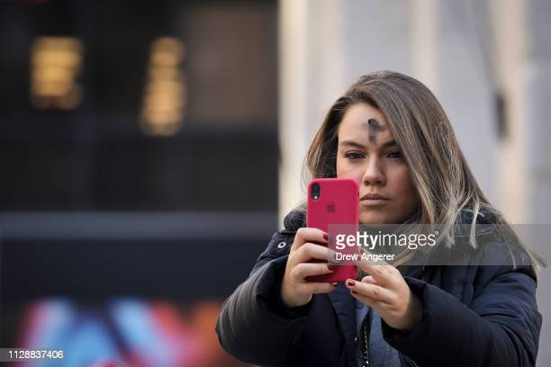 Woman takes a photo of herself as she exits St. Patrick's Cathedral after receiving a cross of black ashes on her head for Ash Wednesday, March 6,...
