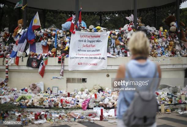 A woman takes a photo of plush toys and posters lying on the 'Promenade des Anglais' in Nice France 14 September 2016 A 31yearold Tunisian man had...