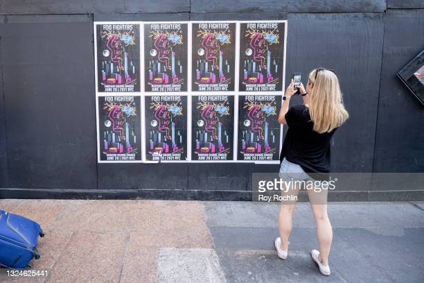 Woman takes a photo of posters for the Foo Fighters show outside as Madison Square Garden reopens with the first full capacity concert since March...
