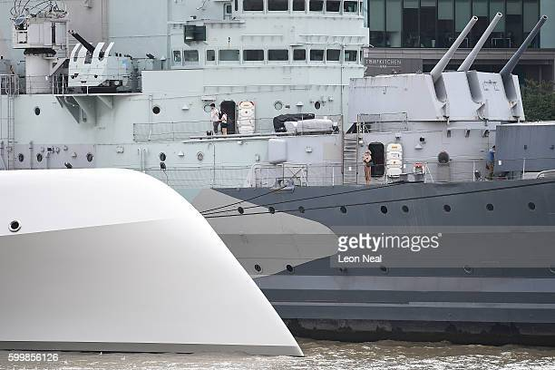 A woman takes a photo of Russian billionaire Andrey Melnichenko's £225m Philippe Starckdesigned boat as it lays moored next to HMS Belfast on the...