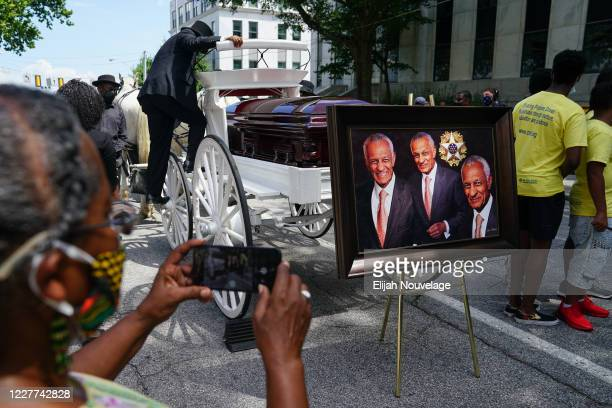 Woman takes a photo of the casket bearing the remains of Civil Rights leader C.T. Vivian outside the Georgia Capitol building on July 22, 2020 in...
