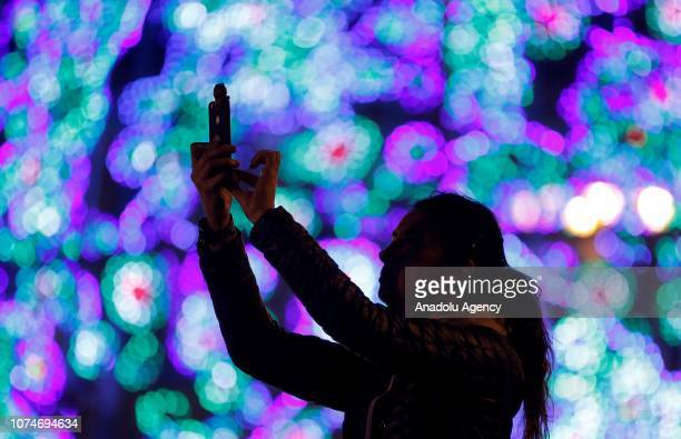 Woman takes a photo of the lights of Puerta del Sol Square ahead of the new year in Madrid, Spain on December 23, 2018.
