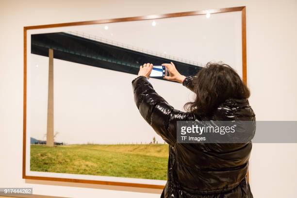 A woman takes a photo of the piece called 'Ruhrtal' by Andreas Gursky in the reopened Hayward Gallery on January 24 2018 in London England