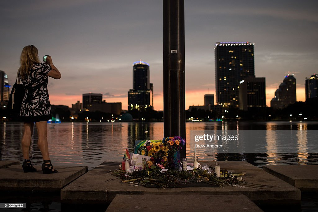 A woman takes a photo of the sunset next to a small memorial for the victims of the Pulse Nightclub shooting, at Lake Eola, June 14, 2016 in Orlando, Florida. The shooting at Pulse Nightclub, which killed 49 people and injured 53, is the worst mass-shooting event in American history.