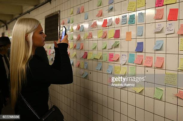 A woman takes a photo of the wall as the people write their messages on selfstick paper as a part of Voice Actor Matthew Chavez's public art project...