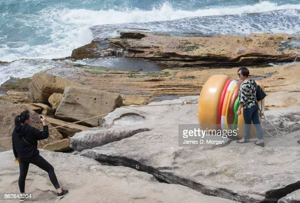 A woman takes a photo of their mother beside 'What a Tasty Looking Burger' by James Dive at Sculpture By The Sea on October 18 2017 in Sydney...