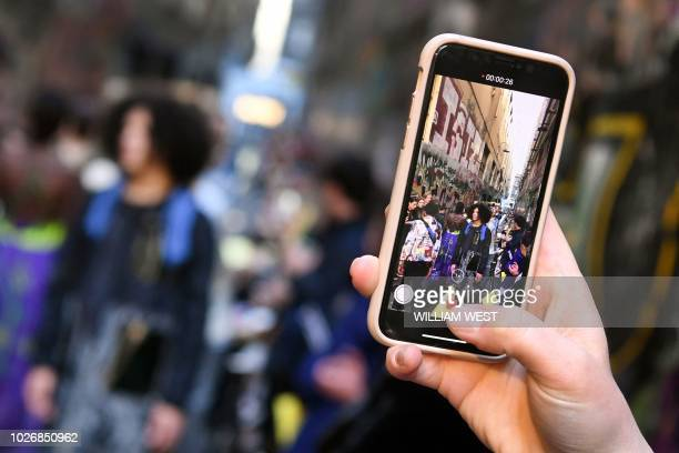 TOPSHOT A woman takes a photo on her phone of models parading outfits by Australian label Asiyam during a Melbourne Fashion Week show in an innercity...