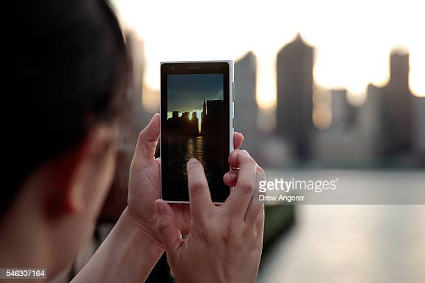 A woman takes a photo on her smart phone of the 'Manhattanhenge' sunset from Hunters Point South Park July 11 2016 in the Queens borough of New York...