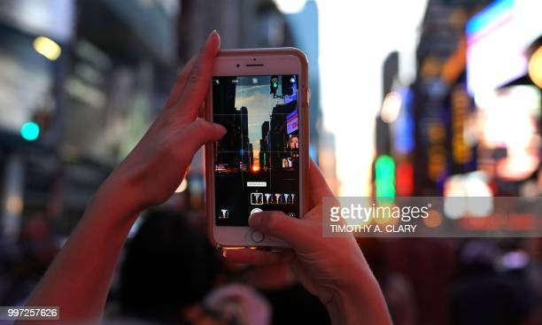 A woman takes a photo with her mobile phone as the sun sets as seen from 42nd street in Times Square in New York City on July 12 2018 during...