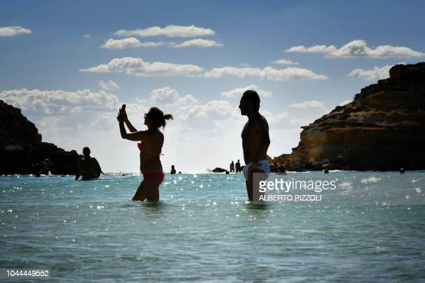 A woman takes a photo with her mobile phone as tourists bathe on the beach of the Isola dei Conigli in Lampedusa on September 27 2018 Five years...