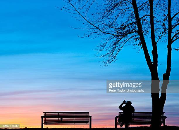 Woman takes a photo with her smart phone at sunset.