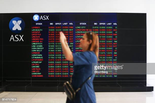 A woman takes a photograph as an electronic board displays stock information at the Australian Securities Exchange operated by ASX Ltd in Sydney...