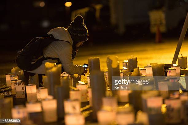 A woman takes a photograph during a ceremony to commemorate the victims on March 11 2015 in Minamisoma Fukushima prefecture Japan On March 11 Japan...