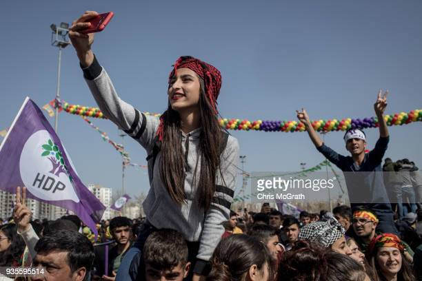 A woman takes a photograph during Nowruz festivities on March 21 2018 in Diyarbakor Turkey Nowruz meaning new day is widely celebrated by Kurdish...