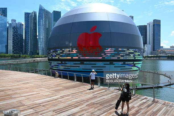 Woman takes a photograph for a friend in front of the new Apple store, located in the water in front of the Marina Bay Sands, in Singapore on August...