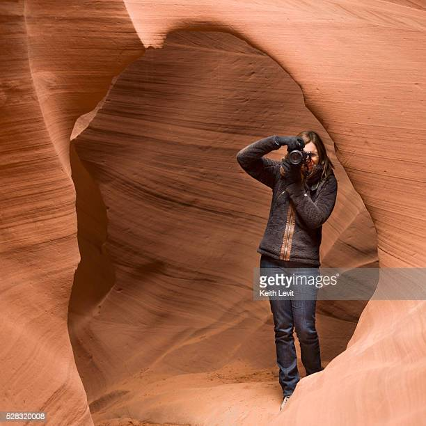 a woman takes a photograph in antelope canyon; arizona united states of america - ロウワーアンテロープ ストックフォトと画像