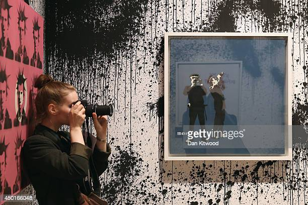 Woman takes a photograph in front of a piece of work entitled 'Avon and Somerset Constabulary' during a press preview of the first unauthorized...
