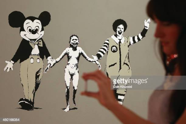 A woman takes a photograph in front of a piece of work entitled 'Napalm ' during a press preview of the first unauthorized retrospective of works by...