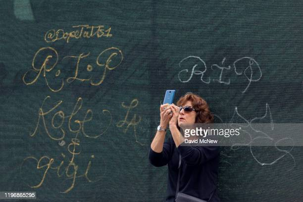 A woman takes a photograph near graffiti that memorializes former NBA star Kobe Bryant and his daughter Gigi who were killed in a helicopter crash in...