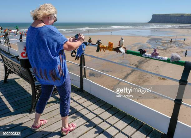 A woman takes a photograph of a display of knitting attached to railings that was left by a secretive group of knitters for their latest display as a...