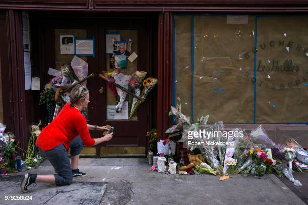 A woman takes a photograph of flowers notes and photographs left in memory of Anthony Bourdain at the closed location of Brasserie Les Halles where...